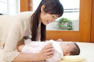 赤ちゃんの顔を見て微笑む母親